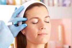 Frau in Schönheitsklinik bekommt eine Spritze gegen Augenfalten